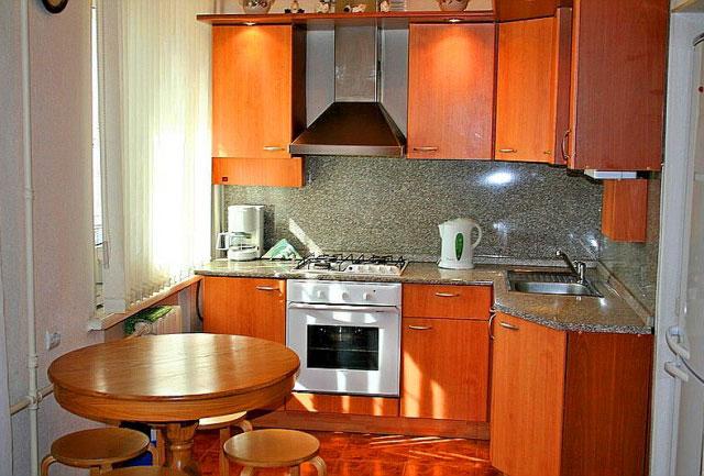Дизайн маленькой угловой кухни с окном и холодильником