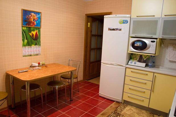 Обеденная зона на угловой кухне желтого цвета - фото
